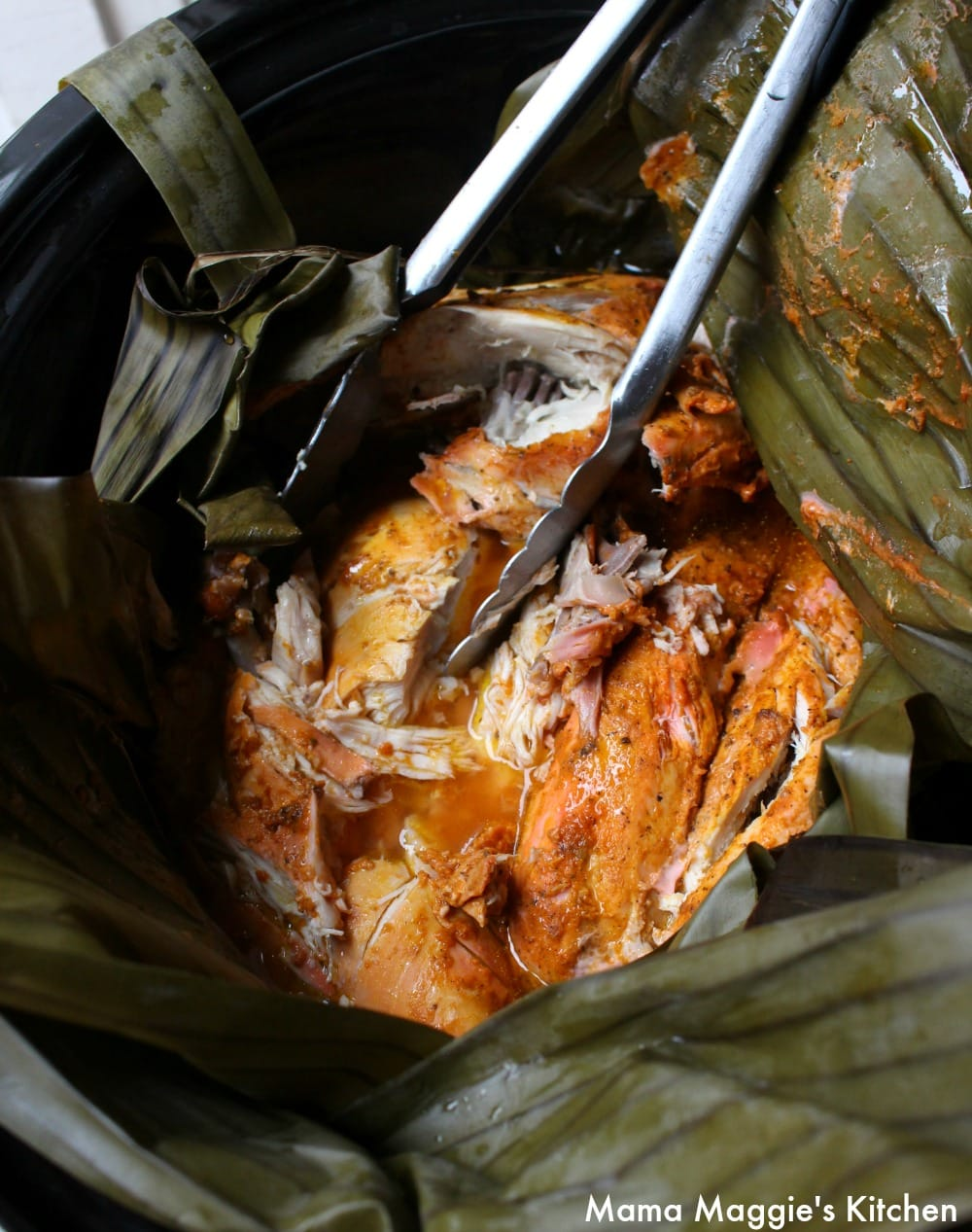 Tongs removing the cooked Pollo Pibil that is still inside the banana leaves.