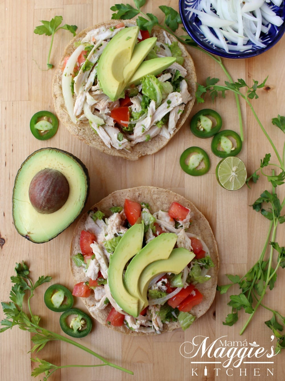 Two tostadas of Salpicon de Pollo topped with avocado slices and surrounded by cilantro leaves and jalapenos.