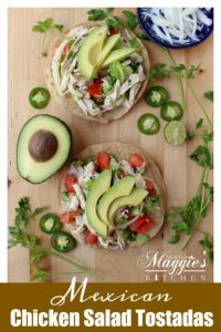 Two tostadas topped with Salpicon de Pollo topped with avocado slices surrounded by cilantro and jalapeno.