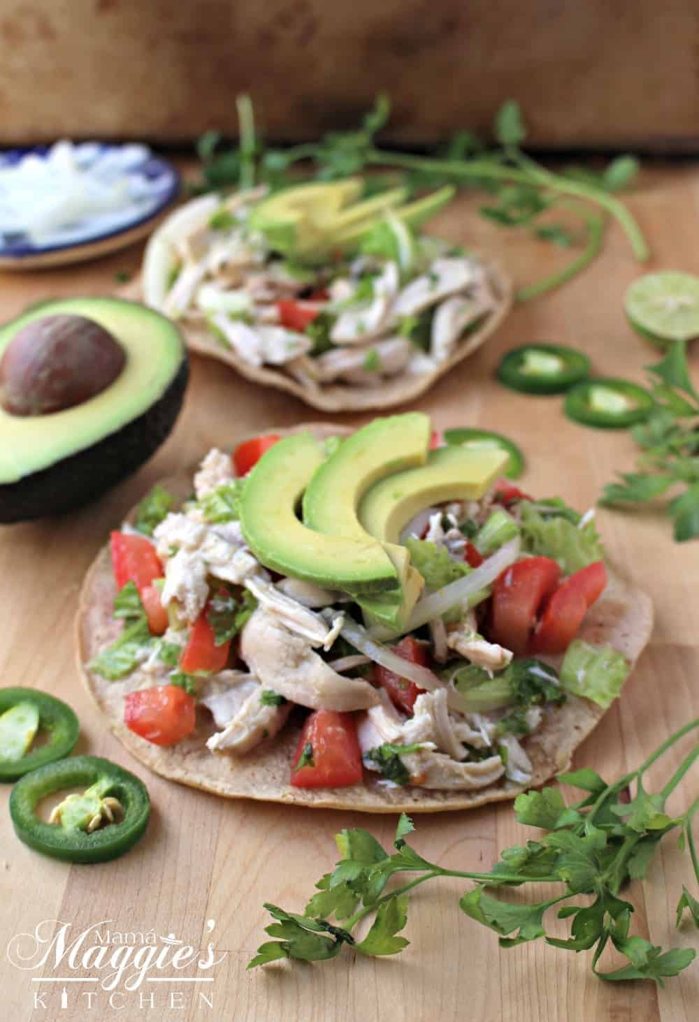 A tostada of Salpicon de Pollo topped with avocado slices surrounded by cilantro and jalapeno.