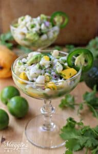 Scallop ceviche in a champagne glass surrounded by cilantro and lime.