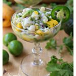 Scallop Ceviche in a champagne glass surrounded by cilantro leaves and lime.