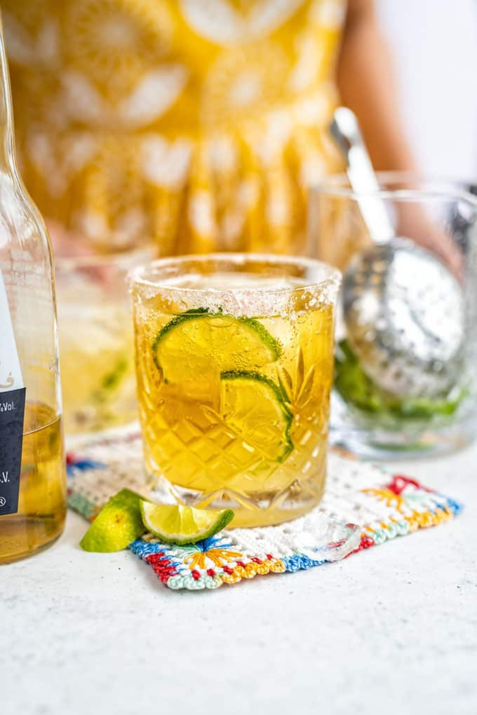 Someone pouring a Beergarita cocktail into a glass with ice and lime wedges.