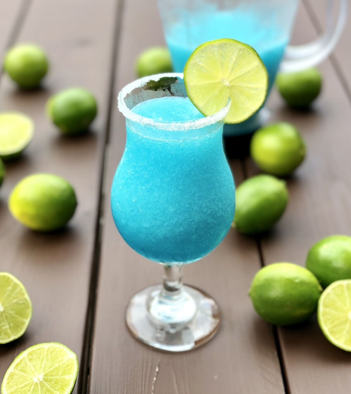 Blue Lagoon Margarita surrounded by lime.