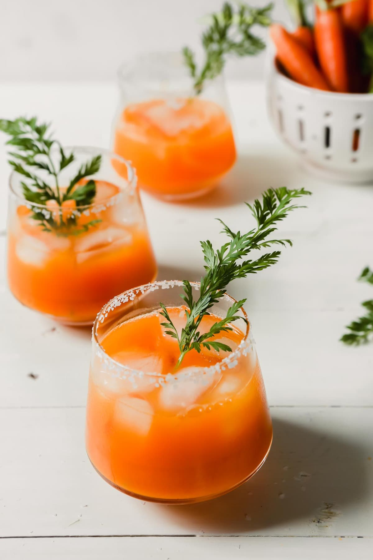 Carrot Cocktail Margaritas topped with green herbs and in glasses with ice.