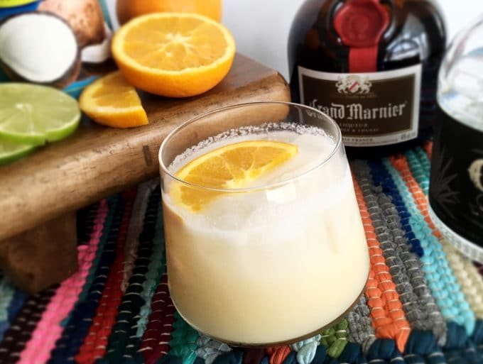 Coconut Orange Margarita topped with an orange slice and surrounded by a bottle of grand mariner and other ingredients.