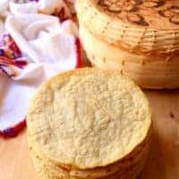 A stack of corn tortillas next to a tortilla holder and decorative kitchen towel.