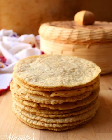 A stack of homemade corn tortillas in front of a tortilla holder.