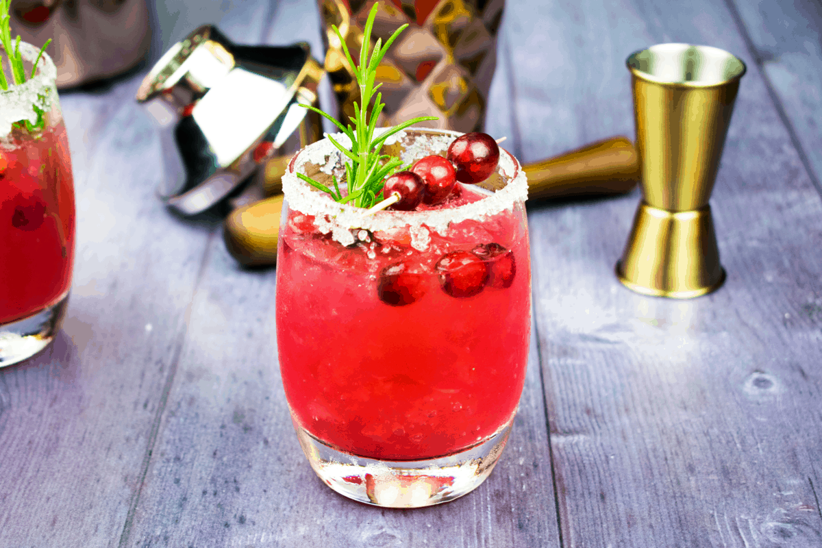 A Skinny Cranberry Margarita topped with a rosemary sprig and whole cranberries.
