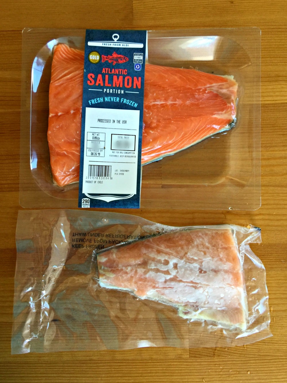 Fresh and frozen salmon side by side on a wooden table.