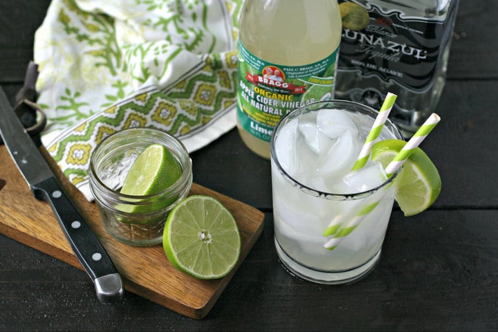 A skinny margarita served in a glass with ice and two straws next to lime wedges.