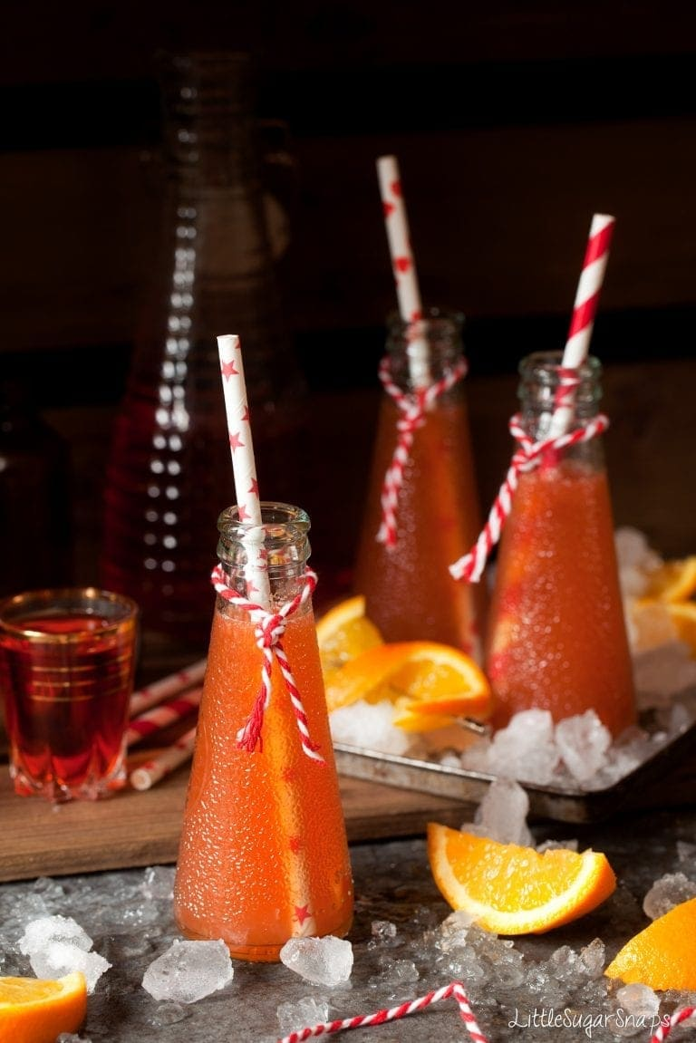 Aperol Tequila Twist served in cone-shaped glasses with red striped straws.