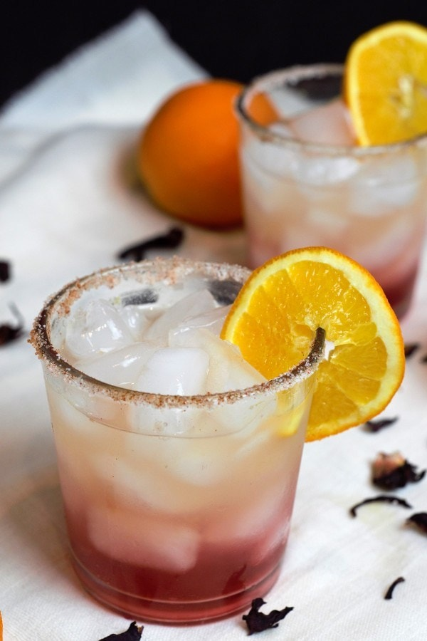 Orange Hibiscus Margarita served in a glass with ice and a slice of orange.