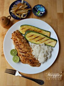 Pescado Sarandeado on a white plate next to grilled veggies and rice.
