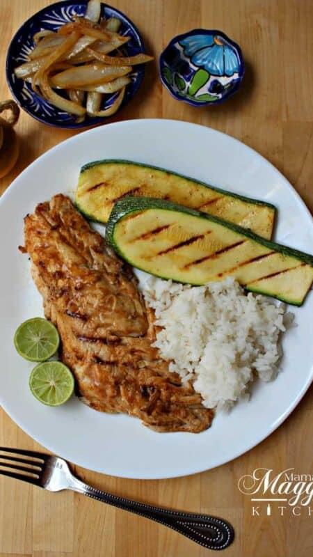 Pescado Sarandeado on a white plate next to grilled veggies and rice.