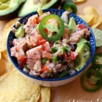 Salmon Ceviche in a bowl topped with a jalapeno slice and surrounded by tortilla chips.