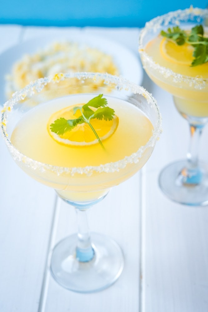 A glass of Meyer Lemon Margarita topped with a lemon slice and cilantro leaf.