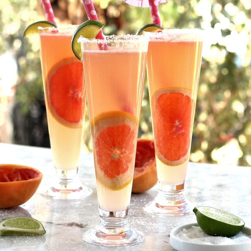 Tequila Lime Spritzer served in champagne flutes with pink straws and lime wedges.