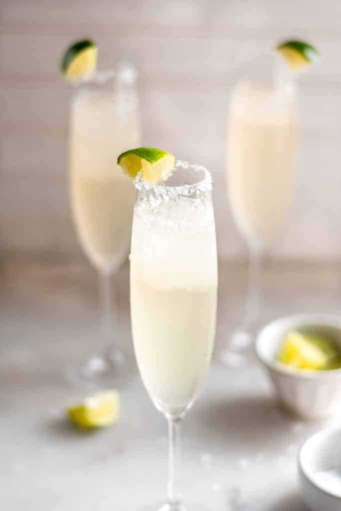Champagne Margaritas served in a champagne flutes and topped with lime wedges.