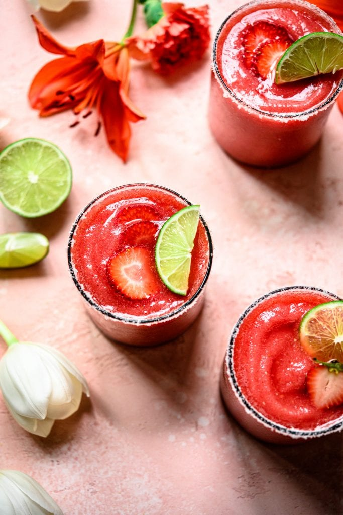 Frozen Watermelon Jalapeño Margaritas topped with green lime wedges on a pink table cloth.