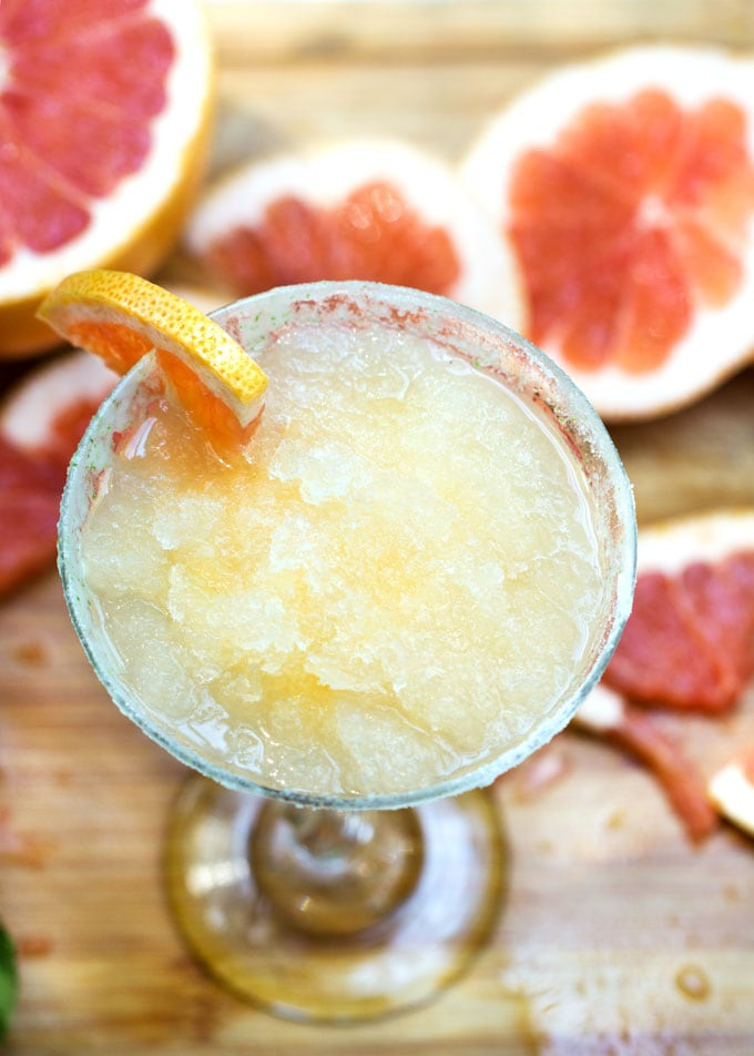 Frozen Grapefruit Margarita topped with a grapefruit slice and surrounded by more grapefruit slices.