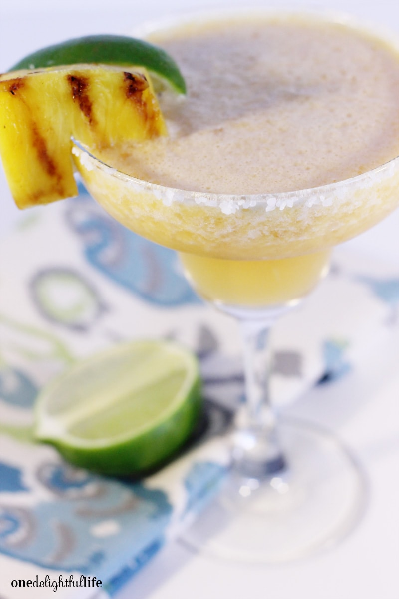 Grilled Pineapple and Peach Silver Tequila Cocktail next to lime wedges and served with a grilled pineapple.