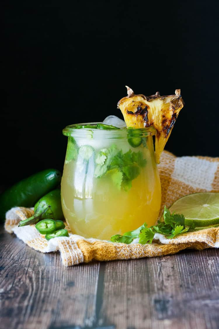 Grilled Pineapple Jalapeno Margarita served in a glass with ice, jalapeno slices, and topped with a grilled pineapple wedge.