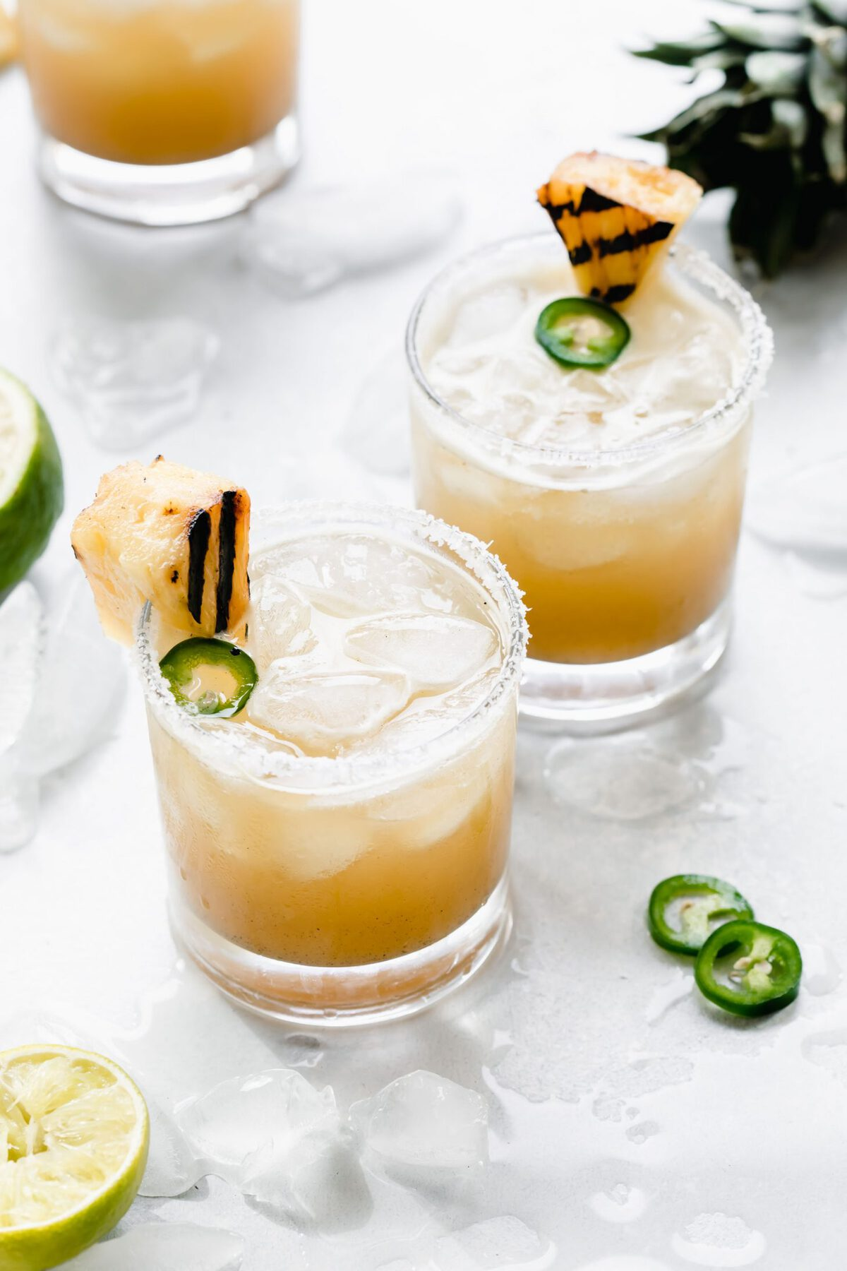 Two Grilled Pineapple Jalapeno Margaritas topped with grilled pineapple and jalapeno slices.