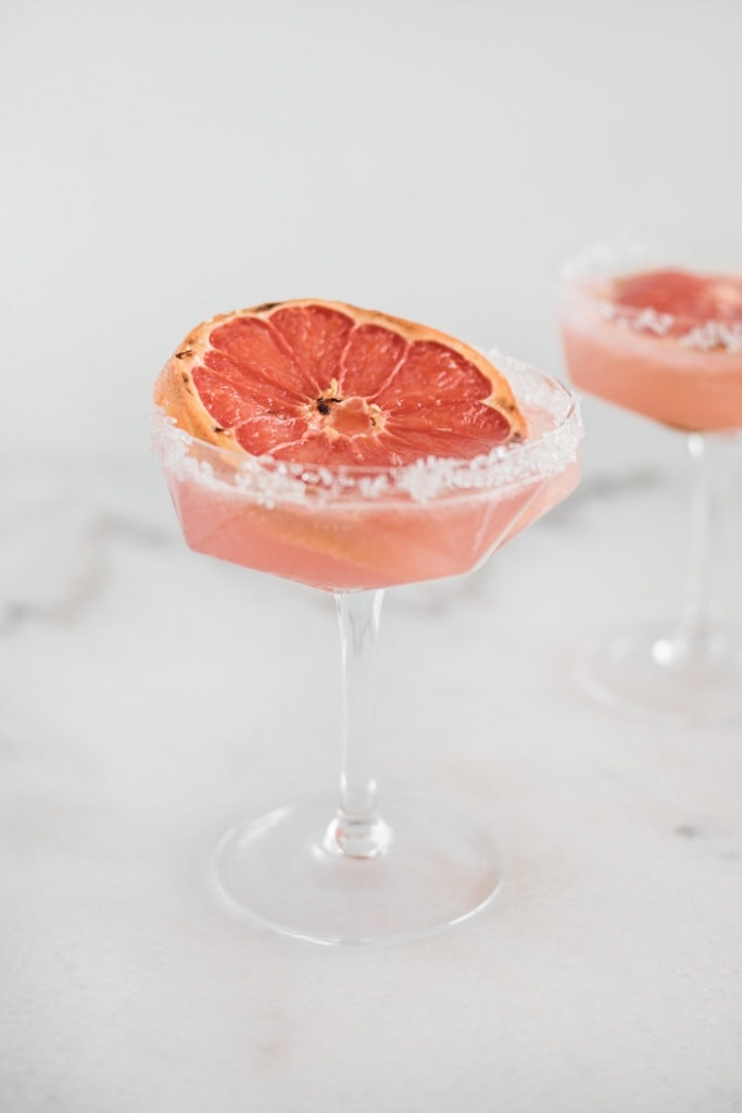 Two Winter Paloma cocktails served in a champagne glass and topped with a grapefruit wedge.