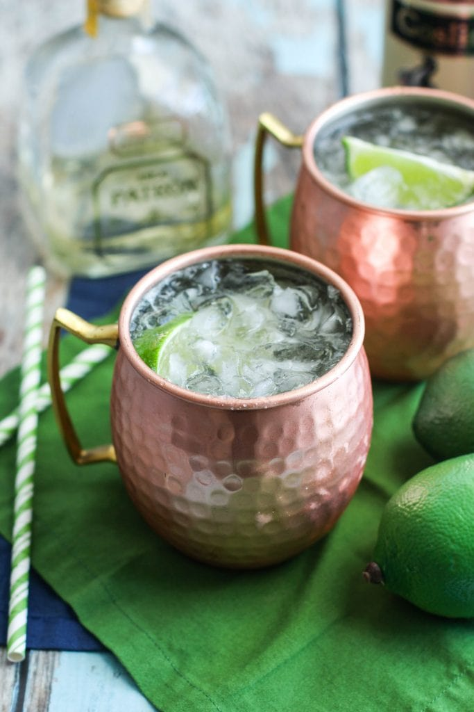 Mexican Moscow Mule served in a copper mugs topped with lime on a green napkin.