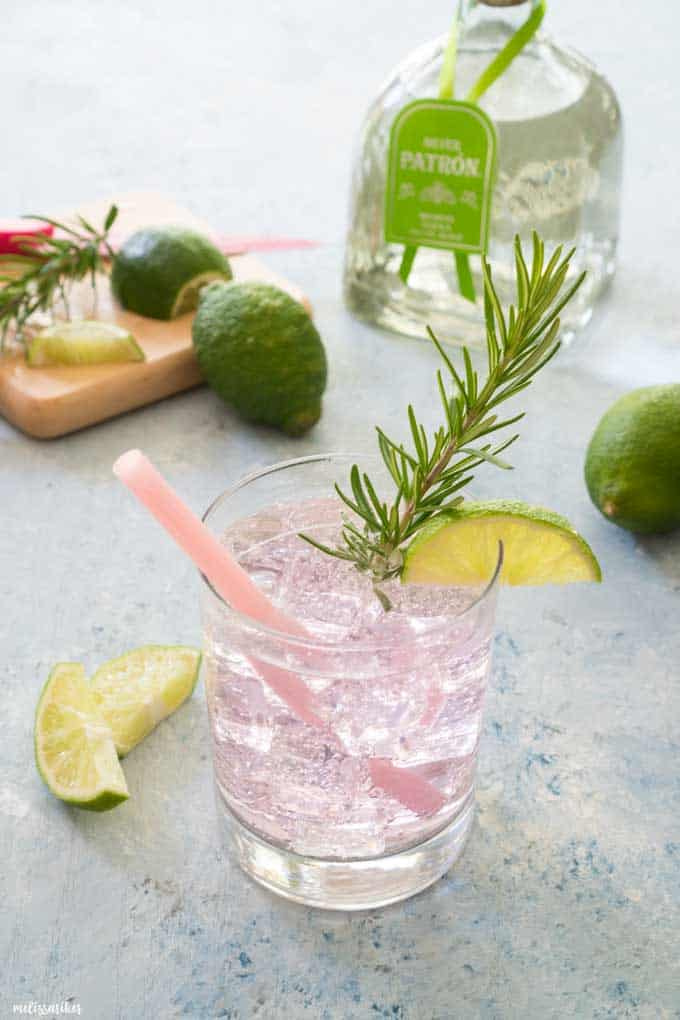 A pink Paloma Cocktail in a glass with ice, lime wedge, and a sprig of rosemary.