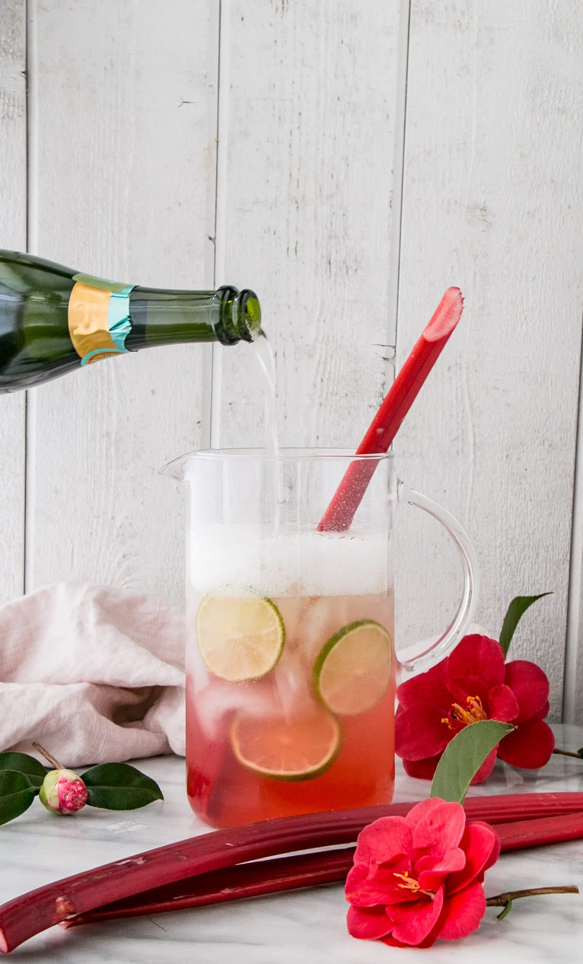 A champagne bottle pouring into a pitcher, making Sparkling Rhubarb Margarita.