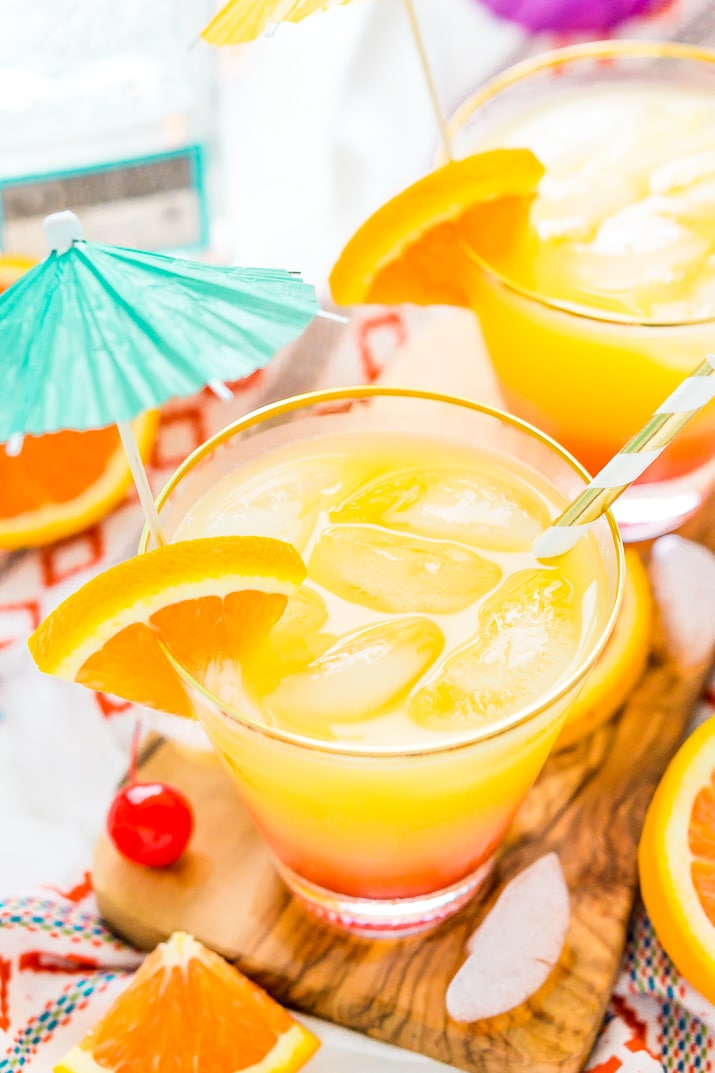 Tequila Sunrise served in a glass with ice and topped with aqua blue umbrella.