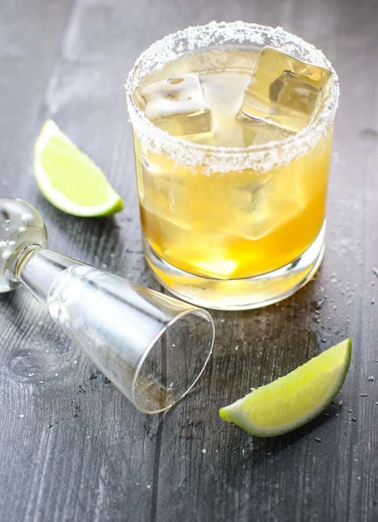 Cadillac Margaritas in salt-rimmed glass surrounded by a shot glass and lime wedges.