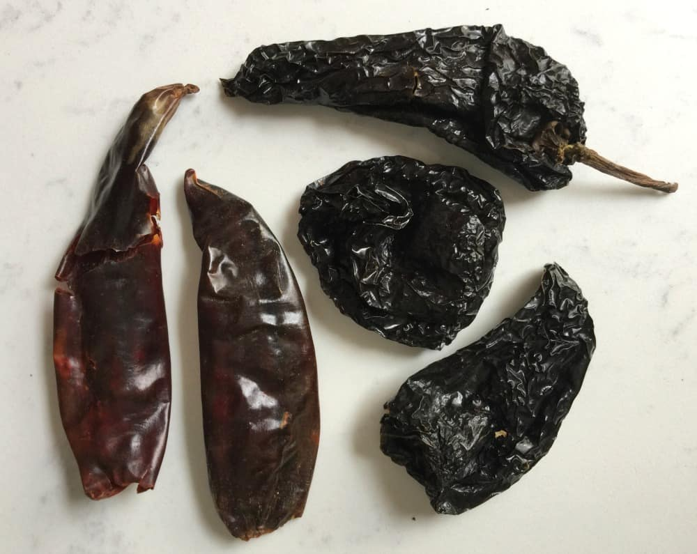 Dried ancho and guajillo chiles on a white marble countertop.