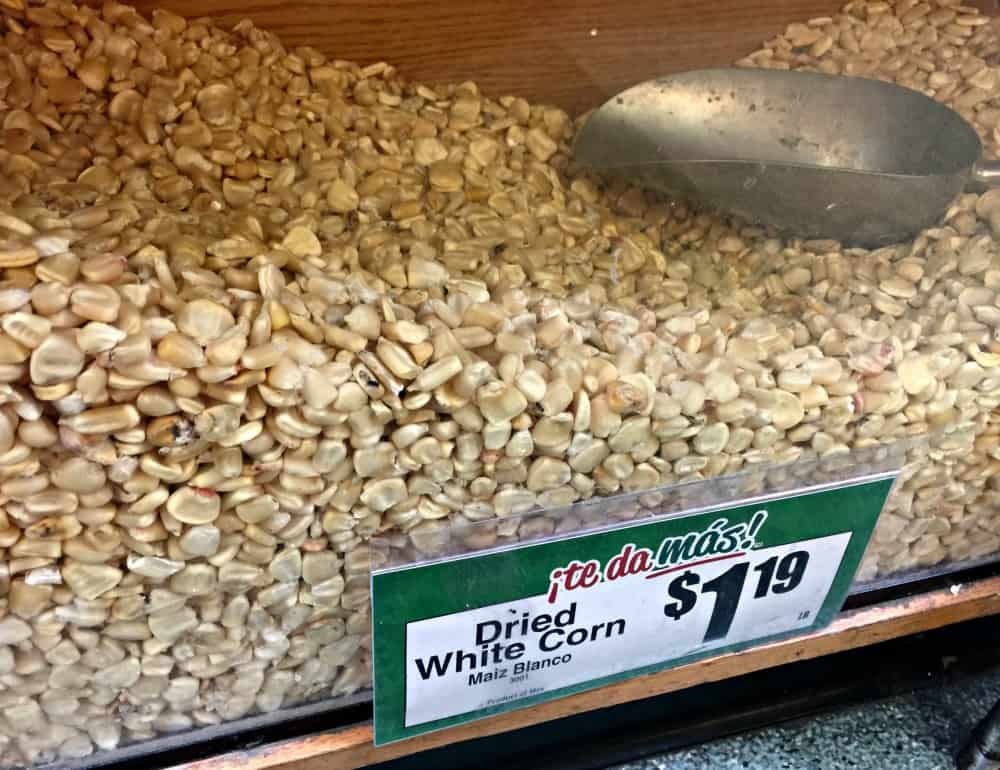 A bin of dried white corn at a grocery store.
