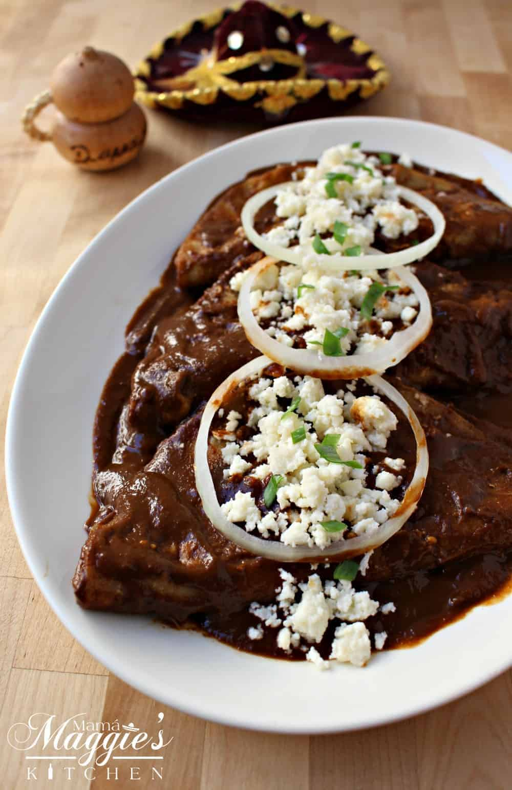 Enchiladas Dulces (Sweet Enchiladas) on a white plate topped with queso fresco and onion slices.
