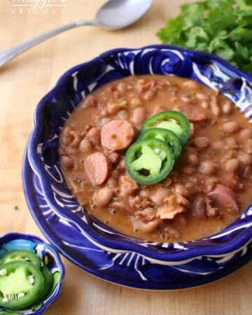 Frijoles Charros in a decorative blue bowl topped with jalapeno slices.