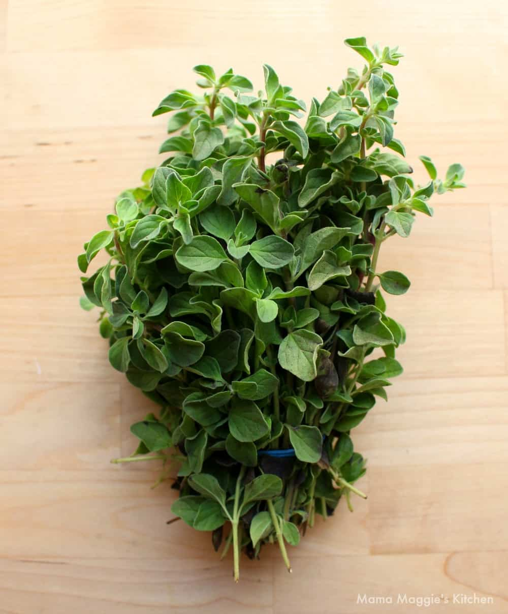 A bundle of fresh oregano on a wooden surface.