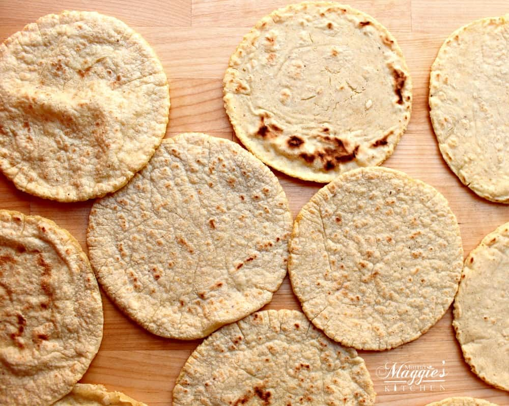 Corn tortillas spread out on a wooden surface.