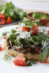 A sope topped with carne asada, lettuce, tomatoes, and cotija cheese.