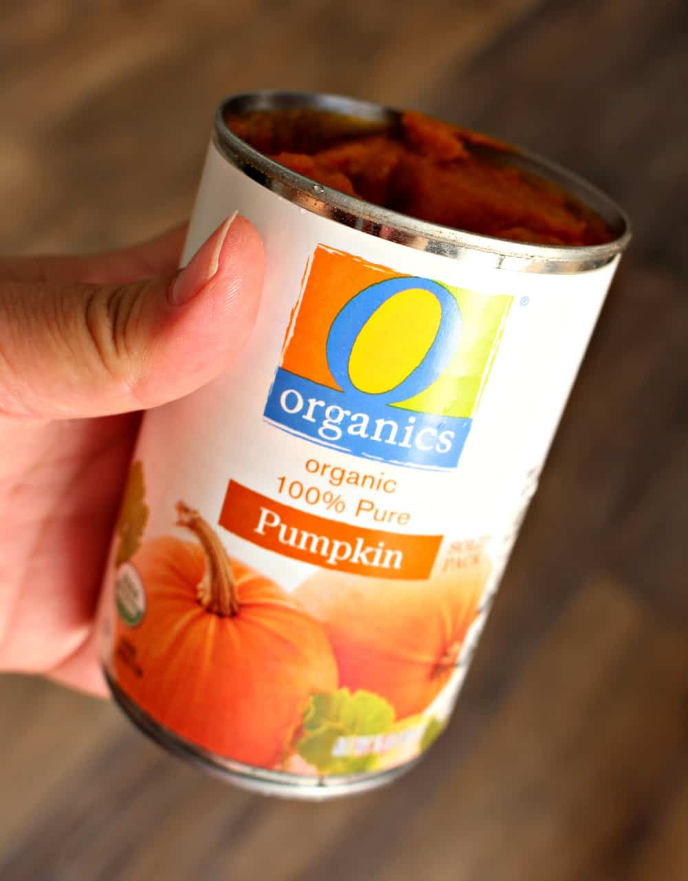 A hand holding a can of pumpkin puree.
