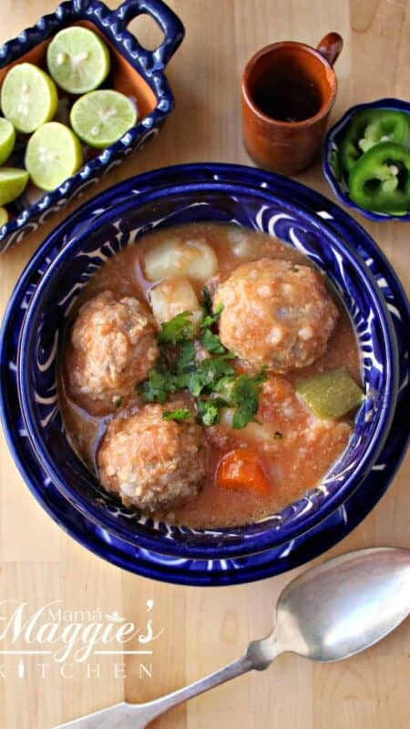 Albondigas en Caldillo (or Mexican Meatball Soup) in a decorative blue bowl next to lime and a spoon.