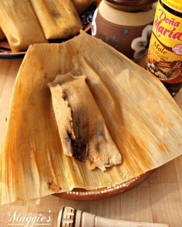 A Tamal de Mole unwrapped but lying on top of the corn husk and next to more tamales.
