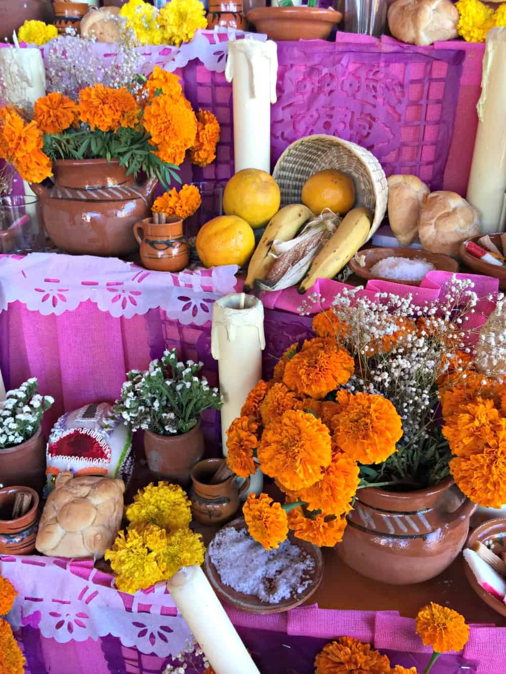 Offerings of bread, flowers, and fruits on a Dia de los Muertos altar.
