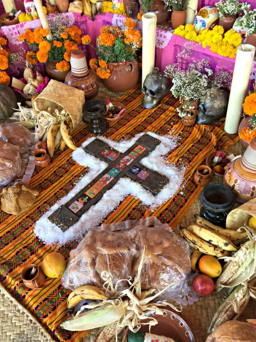 A cross on a Day of the Dead altar surrounded by marigolds, candles, and bread.