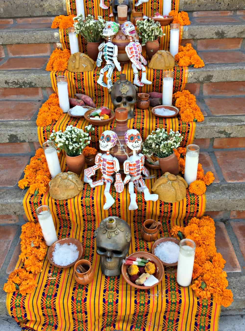 Stairs decorated with skeletons, marigolds, skulls, and candles.