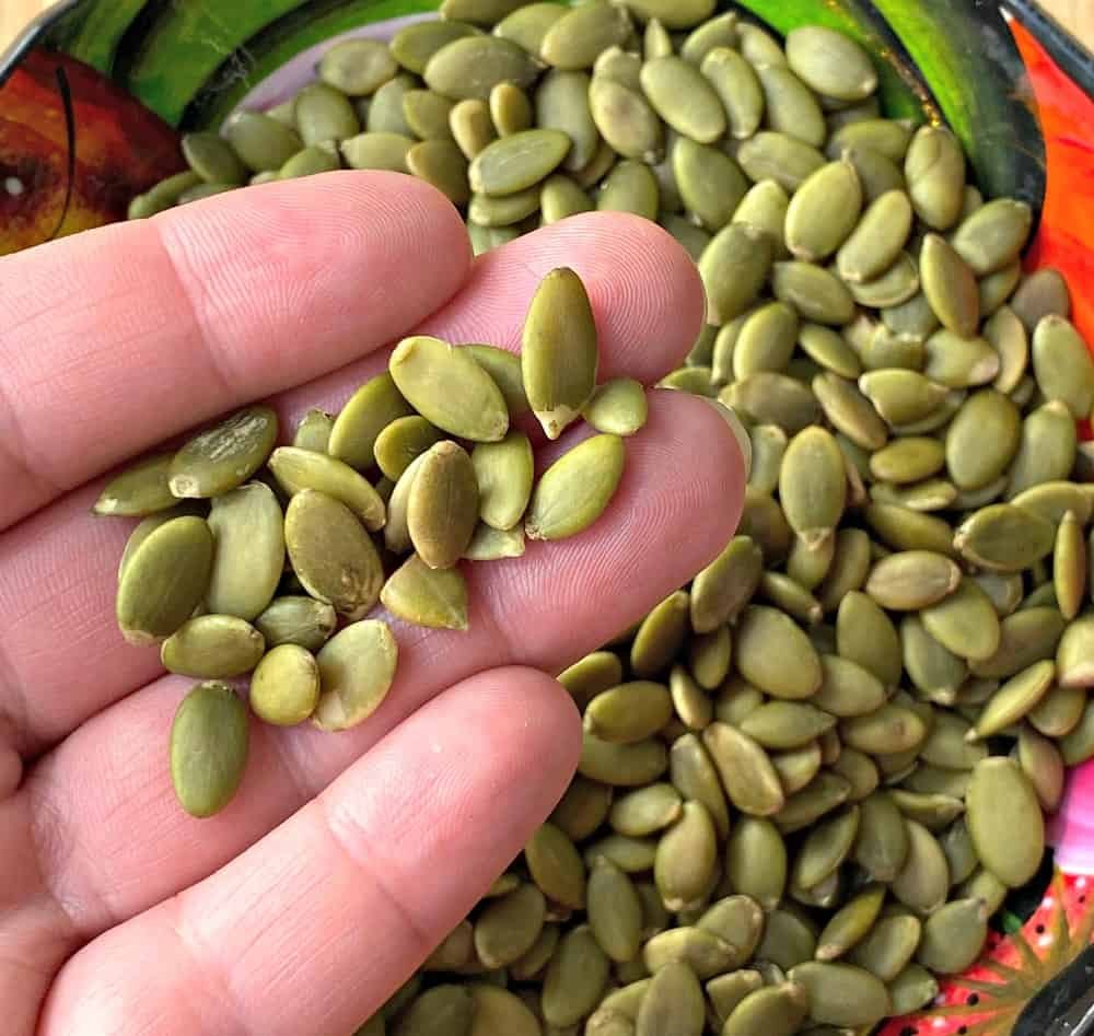 Hand holding pepitas over a pile of pepita seeds.