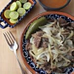 Beef liver and onions in a decorative Mexican plate next to a fork and limes.