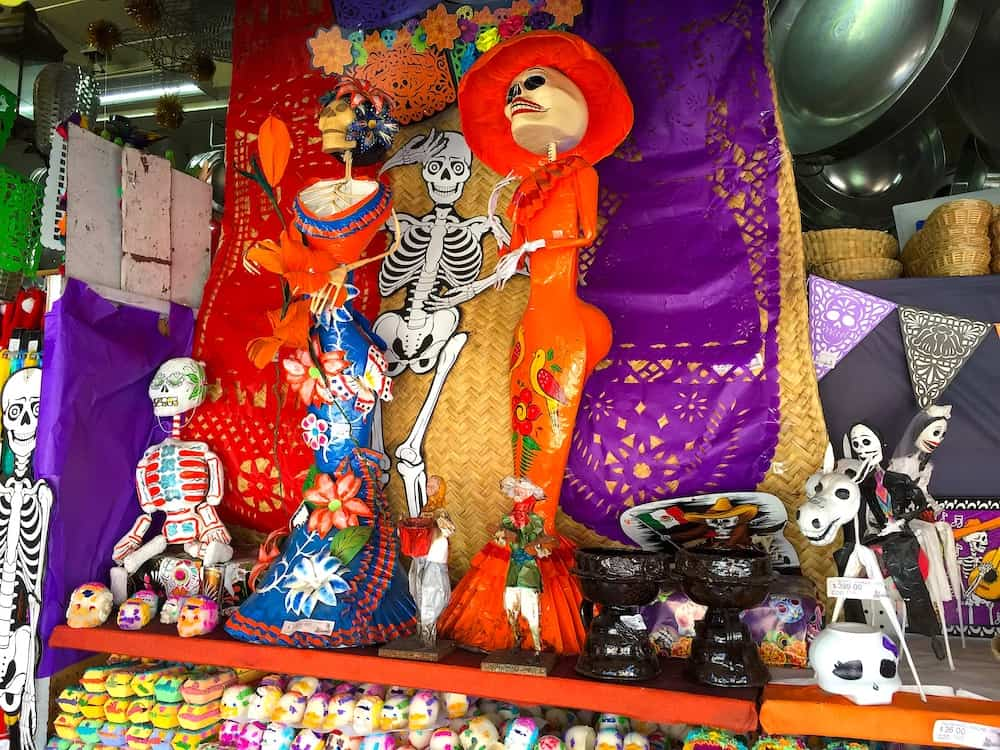 La Catrina standing tall on a Day of the Dead Altar next to sugar skulls.